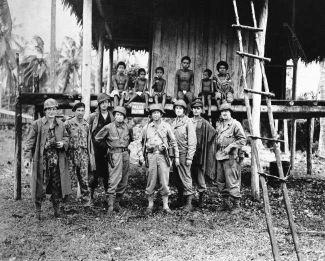 War correspondents covering the allied occupation of Kiriwina Island (Trobiands) line up in front of a native hut in 1943 which served as Press Relations headquarters. Left to right: Peter Hemery, Australian Broadcasting Commission; Frank Bagnall, Australian Department of Information movie photographer; Vern Haugland, Associated Press; Col. Lloyd Lehrbas, GHQ Press Relations Officers; Col. E.P. Herndon, USA; Ed Wallace, National Broadcasting Company; Maj. John Bearman, Australian Press Relations Officer; and Frank Smith of the Chicago. (AP Photo) Ref #: PA.8524949  Date: 01/01/1943