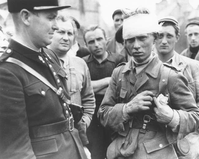 A wounded German soldier who surrendered to the Allied invasion forces, stands surrounded by a crowd of civilians and a French gendarme on the left, in Barneville in the Normandy region, June 1944. (AP Photo)