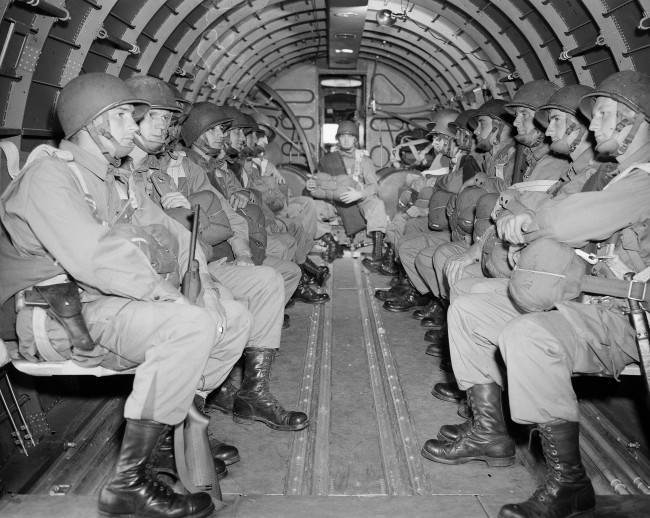 American paratroopers, heavily armed, sit inside a military plane as they soar over the English Channel en route to the Normandy French coast for the Allied D-Day invasion of the German stronghold during World War II, June 6, 1944. (AP Photo)