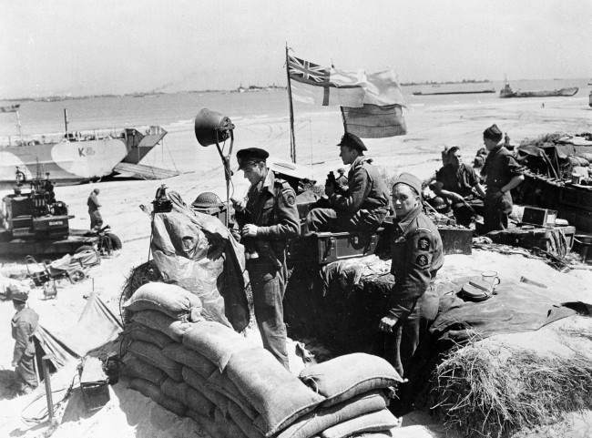 British troops make their way through low water and up the beach after leaving landing craft which transported them across the Channel to the Normandy beachhead for D-Day invasion in France, June 6, 1944 in World War II. (AP Photo/Official British photo)