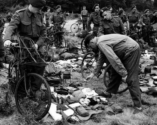 Members of a British special service commando are having their kits checked before leaving for the Allied landing operations of the Normandy coast in France, on June 6, 1944. (AP Photo)