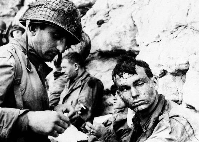 With his hair matted, and a weary but determined look in his face, this American soldier has his hand bandaged by a fellow medical officer, after he was wounded in battle in the early days of the Allied invasion of Normandy, France, in June 1944. (AP Photo)