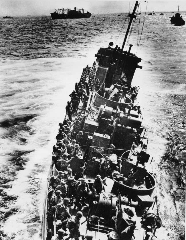 A U.S. Coast Guard LCI, heavily listing to port, moves alongside a transport ship to evacuate her troops, during the initial Normandy landing operations in France, on June 6, 1944. Moments later the craft will capsize and sink. Note that helmeted infantrymen, with full packs, are all standing to starboard side of the ship. (AP Photo)