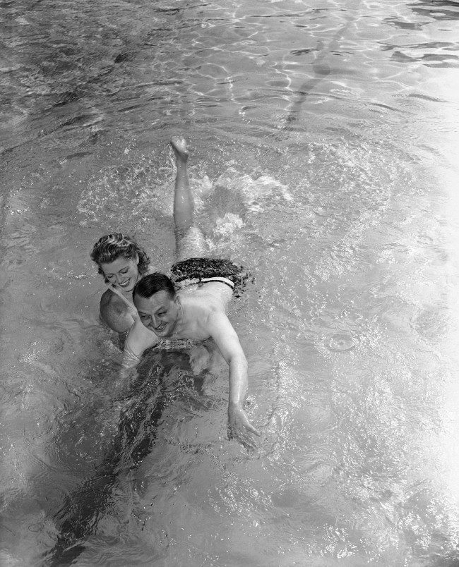 "Larry Allen, Associated Press war correspondent who nearly drowned when the British Cruiser Galatea was torpedoed and sunk, takes his first swimming lesson in Miami, Florida on Feb. 17, 1942, fulfilling a vow he made while struggling for his life in the Mediterranean. Helping him make the lesson a pleasure is his instructor, Peggy Diehl. Larry's ambition was to learn to swim 20 feet, ""Enough to escape the suction of a sinking ship"" but when he met his instructor he raised it to 100 feet. (AP Photo)"