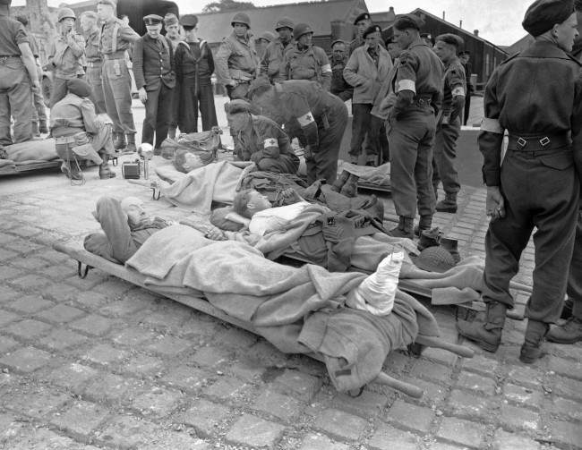 "Some of the first British soldiers wounded in the French invasion coast fighting lie on stretchers somewhere in ""Blighty"" – home in England – brought back the very day the assault started, June 6, 1944. Allied service men look with commiseration on their stricken comrades. (AP Photo/Harry Harris)"