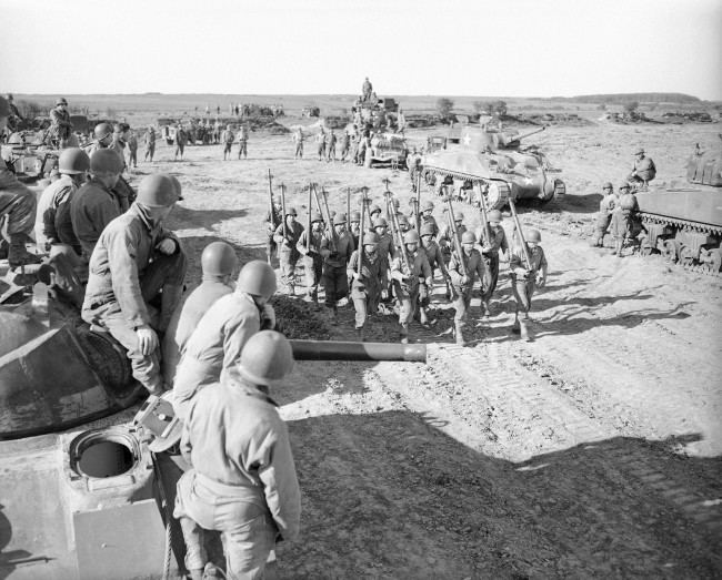 The 'Bazooka Boys', a squad of tank maintenance men practicing on a firing range in England, May 9, 1944, marches through a collection of General Sherman tanks, as the tank crewmen watch, while final invasion preparation are made for D-Day. The range, maintained by the British Royal Armored Corps, has at the British Eighth Army. (AP Photo)