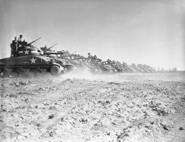 Men of a U.S. tank division line up their General Sherman (M-4) tanks on a range in England to get in a round of firing practice with their 75 mm. guns, as preparations for D-Day reach their climax, May 9, 1944. (AP Photo)