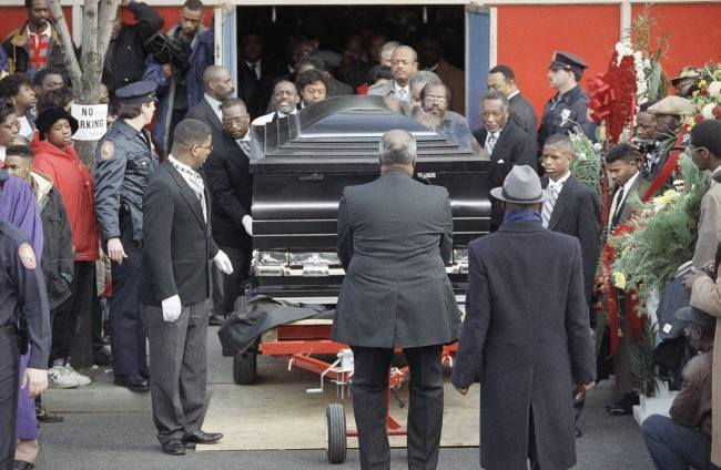Eight pallbearers roll the custom-made casket of Walter Hudson, who weight more then 1,000 pounds when he died, on a metal dolly out of Gospel Blessed Center Church in Hempstead, New York, after funeral services, Jan. 3, 1992. Hudson, who died Christmas Eve of a heart attack, attracted worldwide attention when he lost over 600 pounds several years ago with the help of nutrition guru Dick Gregory. (AP Photo/Mike Albans)