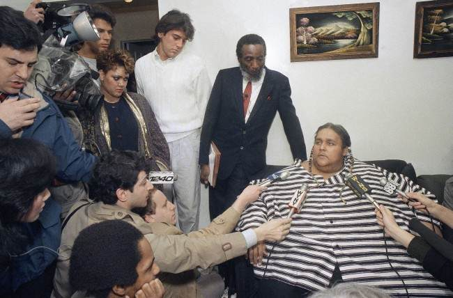 Eight-hundred-pound Walter Hudson explains that he couldn't muster the courage to leave the home he hasn't been out of for 18 years, Feb. 5, 1988 in Hempstead, New York. Hudson, 42, weighed 1,200 pounds a few months ago before going on a diet supervised by Dick Gregory, who stands beside him during the interview. (AP Photo/David Bookstaver)