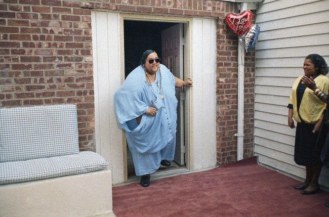 Walter Hudson, who had not walked out of his Hempstead, New York, home for 18 years, takes his first steps outdoors, Sept. 8, 1988. Hudson, who weighed 1,200 to 1,400 pounds, announced he is down to 520 pounds. (AP Photo/Charles Wenzelberg)