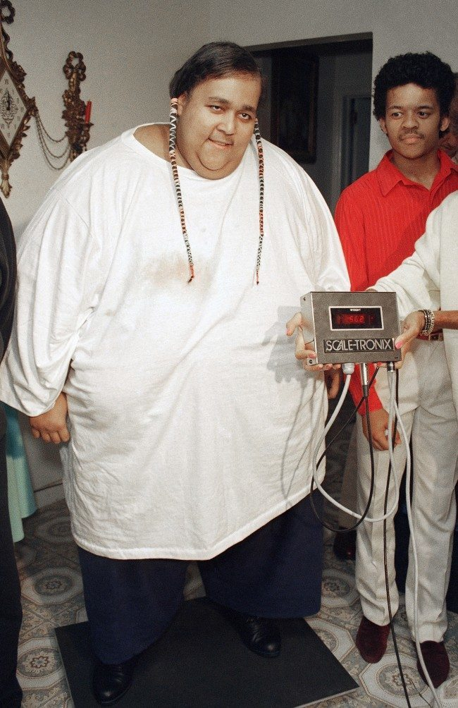 Walter Hudson smiles in New York, July 14, 1988, as he stands on a scale that shows that he now weighs only 562 pounds.