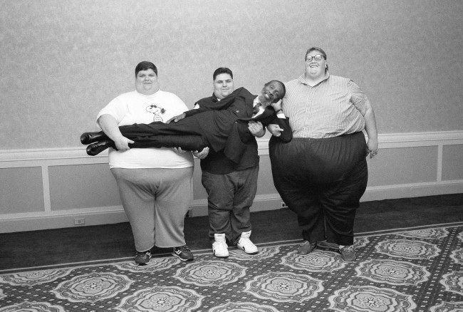 Comedian turned nutritionist Dick Gregory gets a heavy-handed lift, left to right: 526-pound Ron Miller, of Marion, Ind., 375-pound Lou Barone, Elmont, New York, and 750-pound Mike Parteleno, Struthers, Ohio, June 7, 1988 in New York. Gregory has assembled a group of 13 obese people, whose total weight is nearly three tons, in a nutrition program aimed at helping them lose weight.