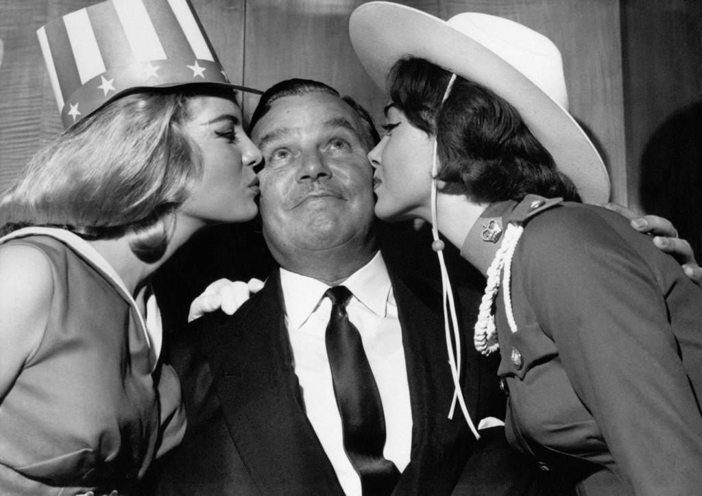 Billy Butlin gets a kiss from Miss America and Miss Canada in 1962.