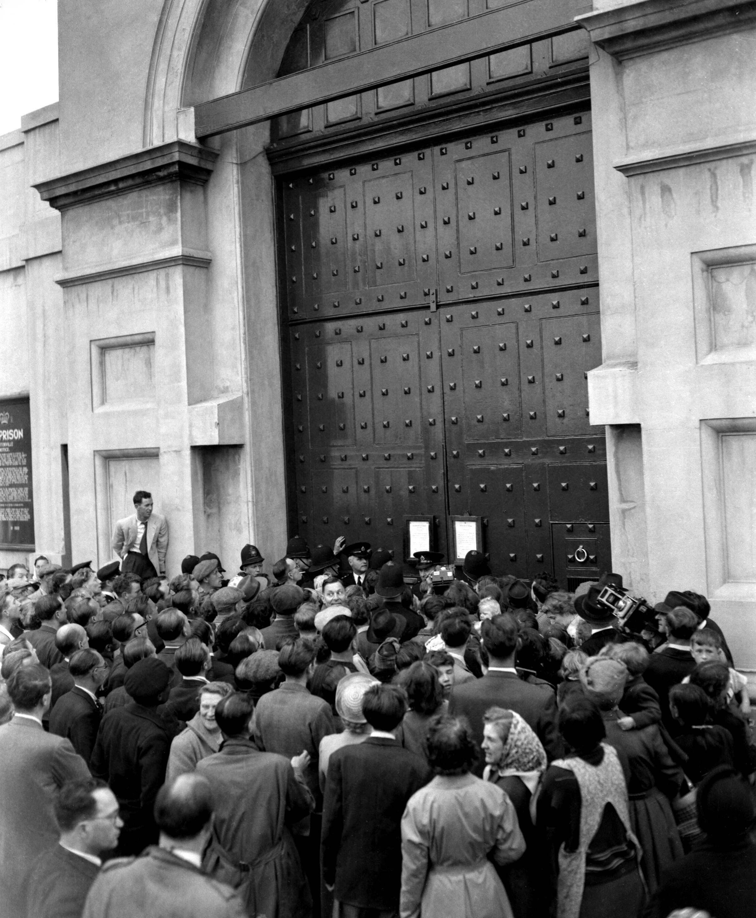 A section of the crowd which gathered outside the gates of Pentoville Prison, London on July 15, 1953 to see the notice of execution for John Reginald Halliday Christie.