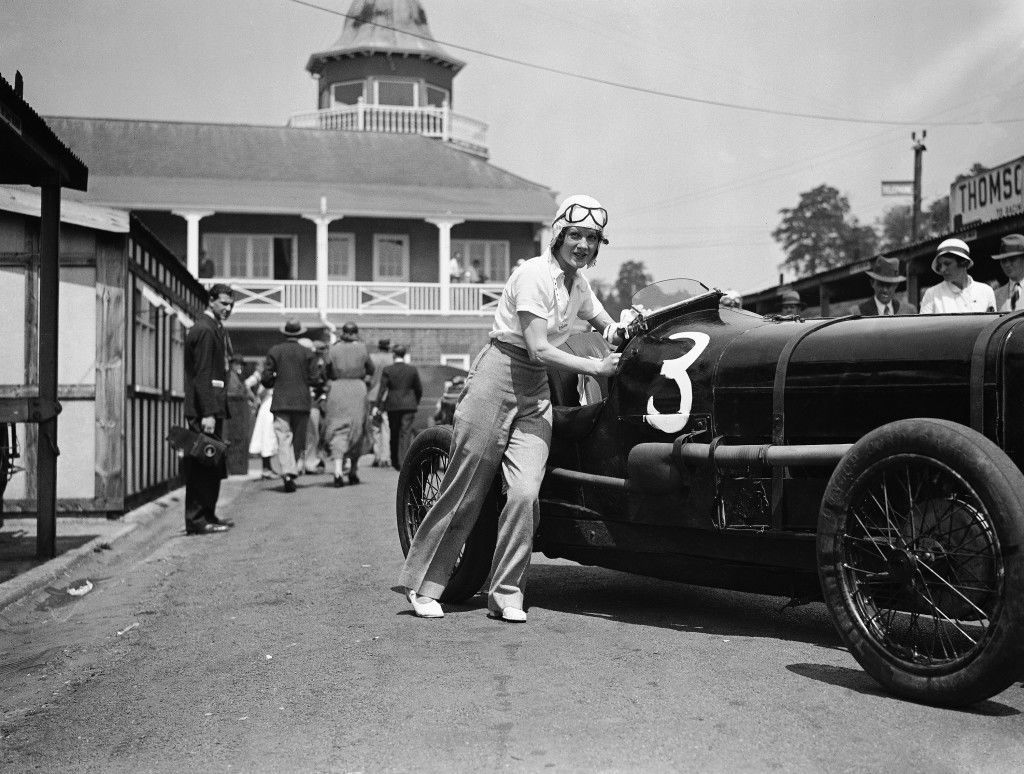 A Big crowd turned up at Brooklands Whit Monday for the fine Holiday motor racing programme. Miss Paddy Maismith pushing her car onto the track for one of the events at Brooklands, England on June 5, 1933. (AP Photo)