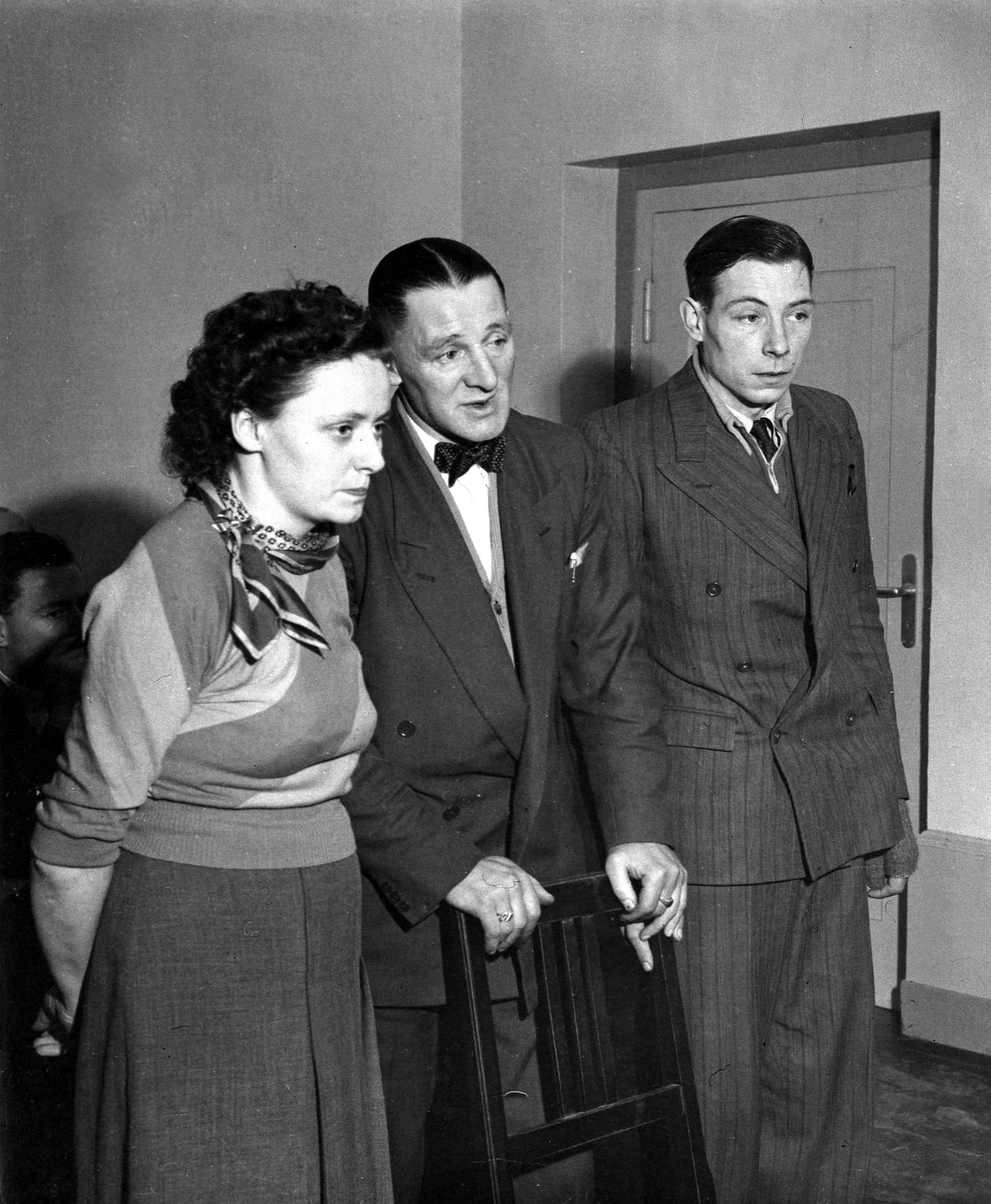 Robert William Ferris, right, and Charles Joseph Coward, centre, both Britons who were prisoners of war at Auschwitz, are seen with a language interpreter as the 'slave labour' lawsuit against German conglomerate IG Farben opens at a court in Frankfurt, Feb. 19, 1953. (AP Photo)