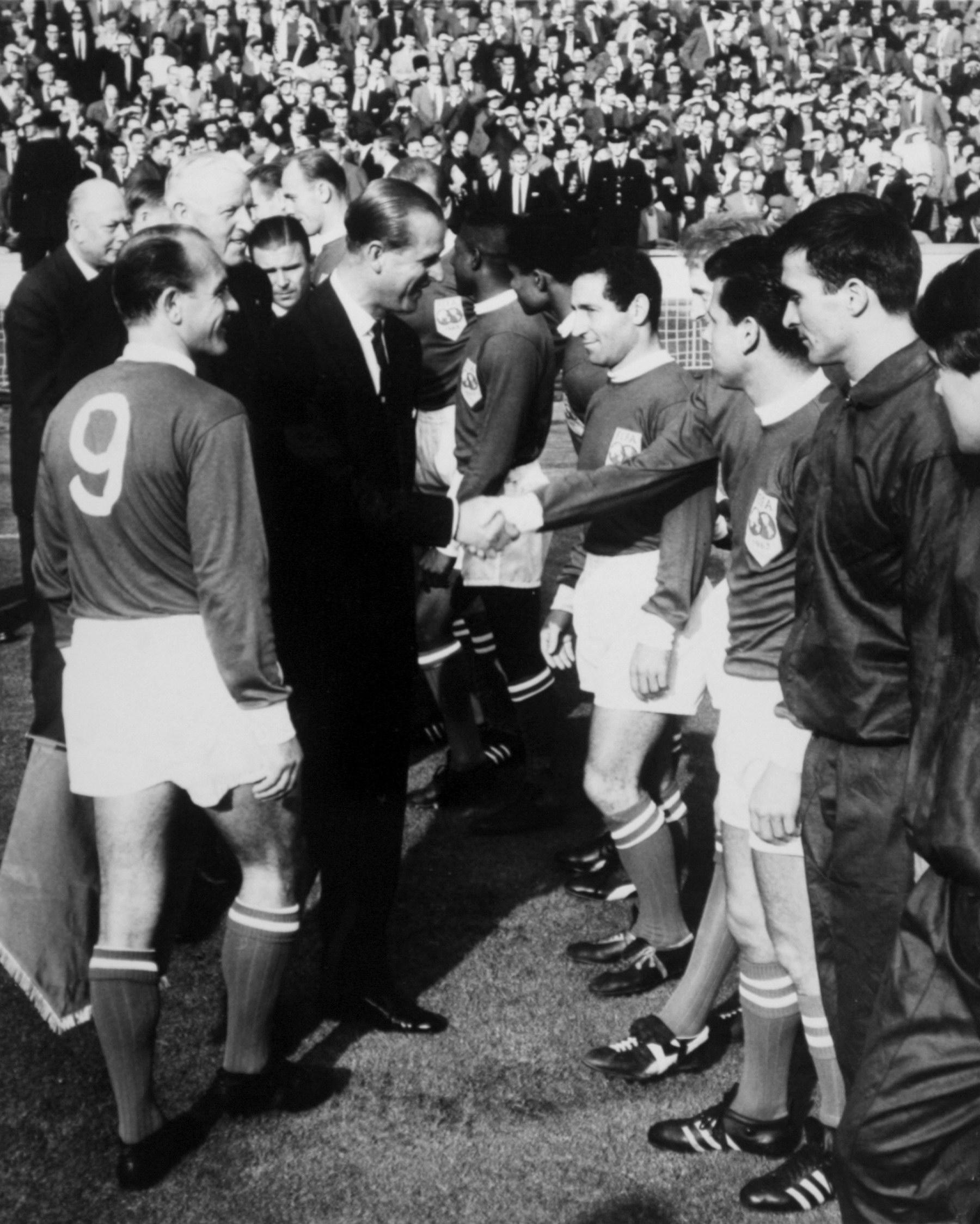 Soccer - FA 100th Anniversary Match - England v Rest of the World Rest of the World captain Alfredo di Stefano (l) looks on as HRH The Duke of Edinburgh shakes hands with Rest of the World's Denis Law (third r). To Law's right stand his teammates Francisco Gento, Eusebio and Djalma Santos Date: 23/10/1963