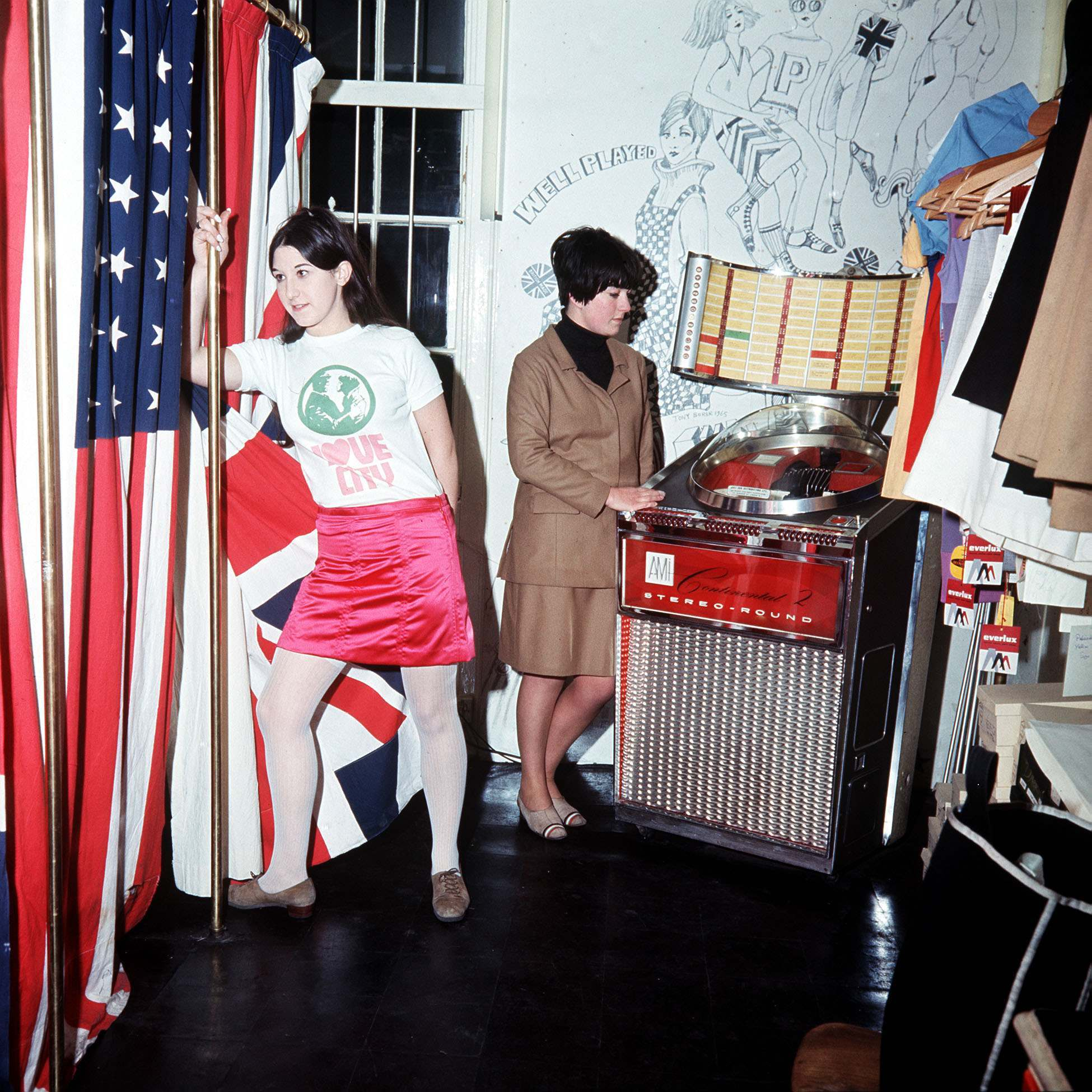 SWINGING LONDON 1966: In Pauline Fordham Ganton Street, near Carnaby Street. Customer Jackie Binder in a 'with it' blouse and skirt stands beside a dressing room decorated with the Union Jack and the Stars and Stripes. In the background, Jacqueline Ball plays the juke box.