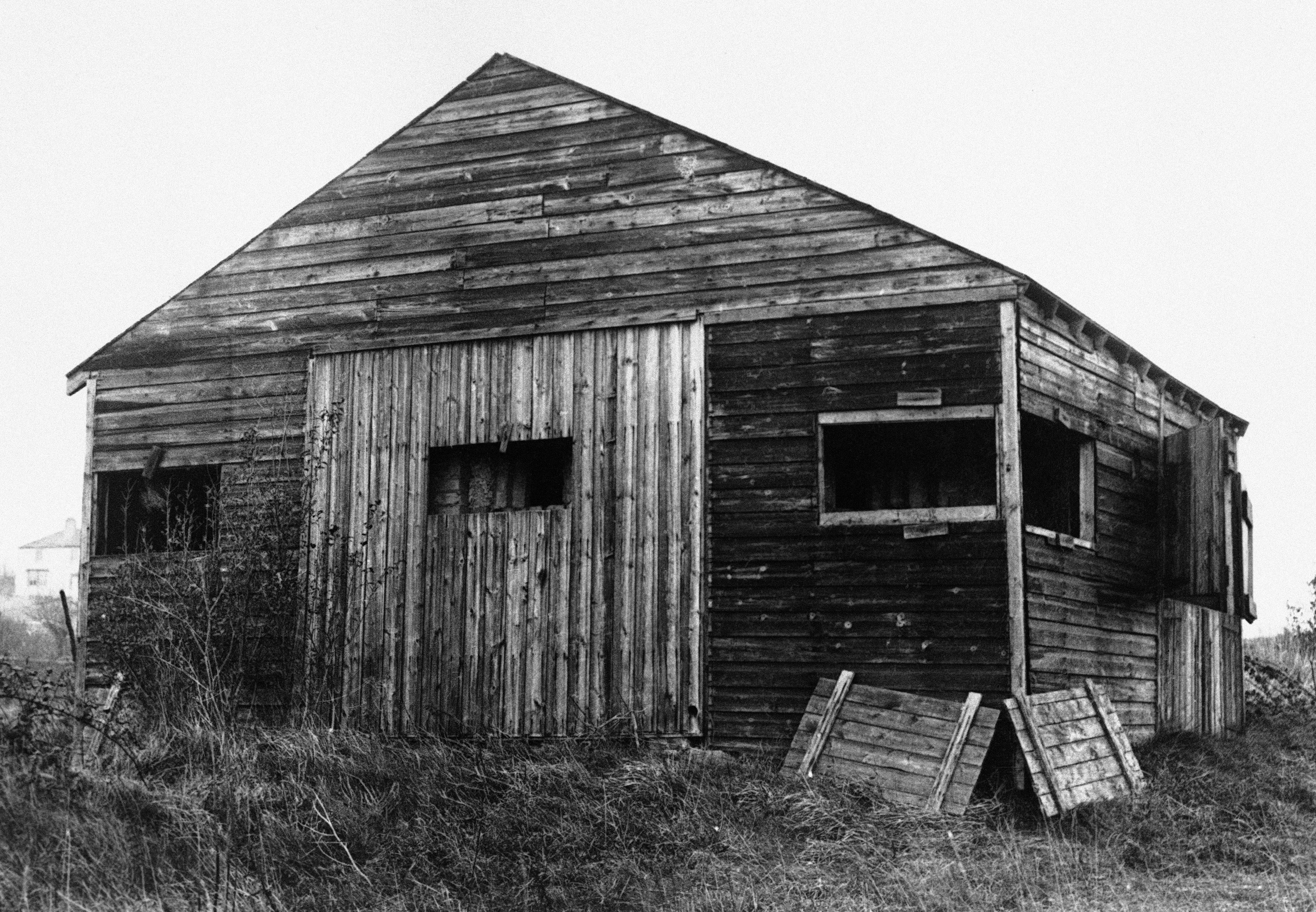 A lonely wooden shack is the simplest kind of pillbox camouflage in an undated photo. After the pillbox is built the shack is built round it. When the pillbox has to start shooting, the shack is knocked down.