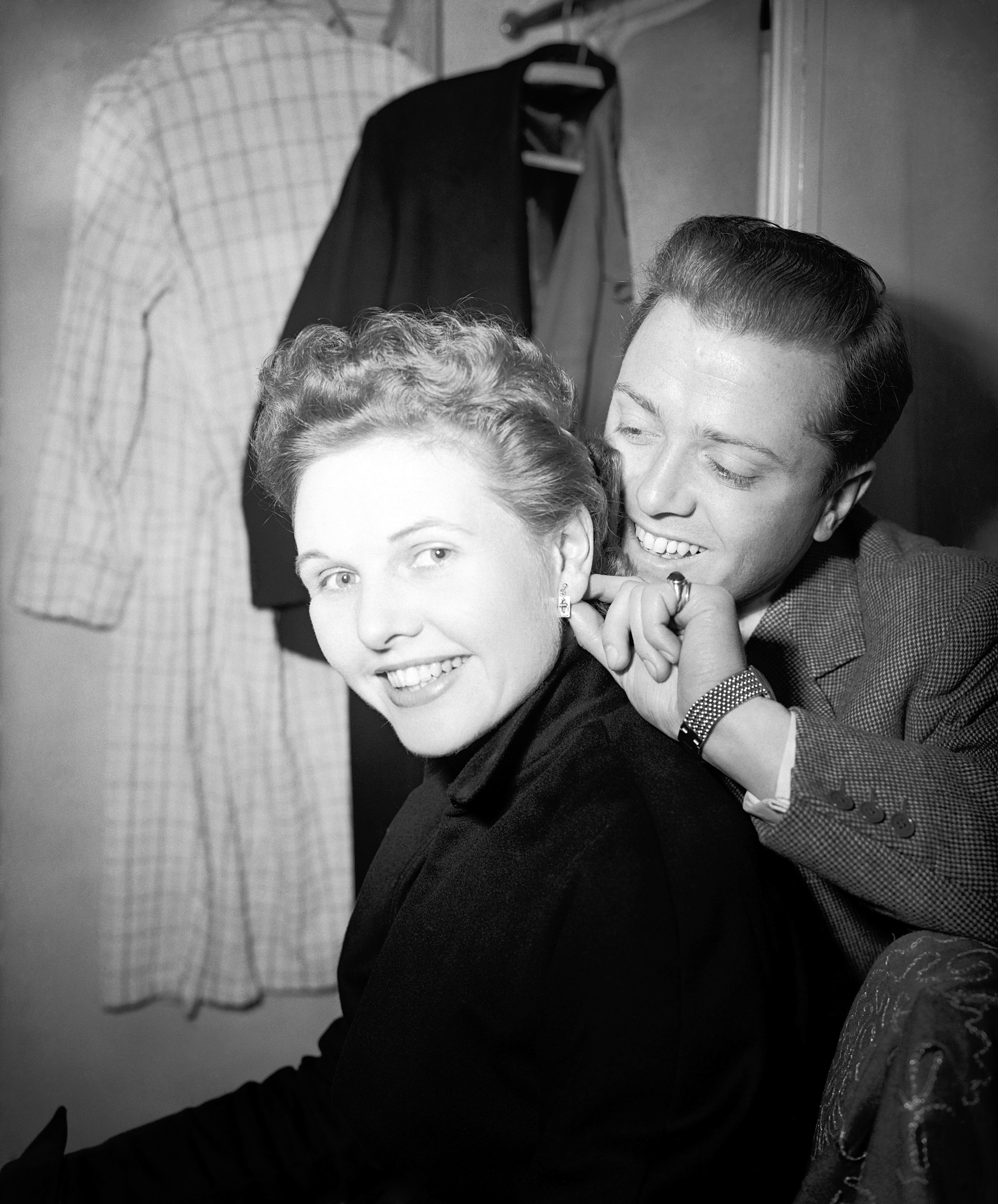 Richard Attenborough gives his wife earrings as a first night present ahead of 'The Mousetrap' opening at The Ambassadors Theatre, 1952.