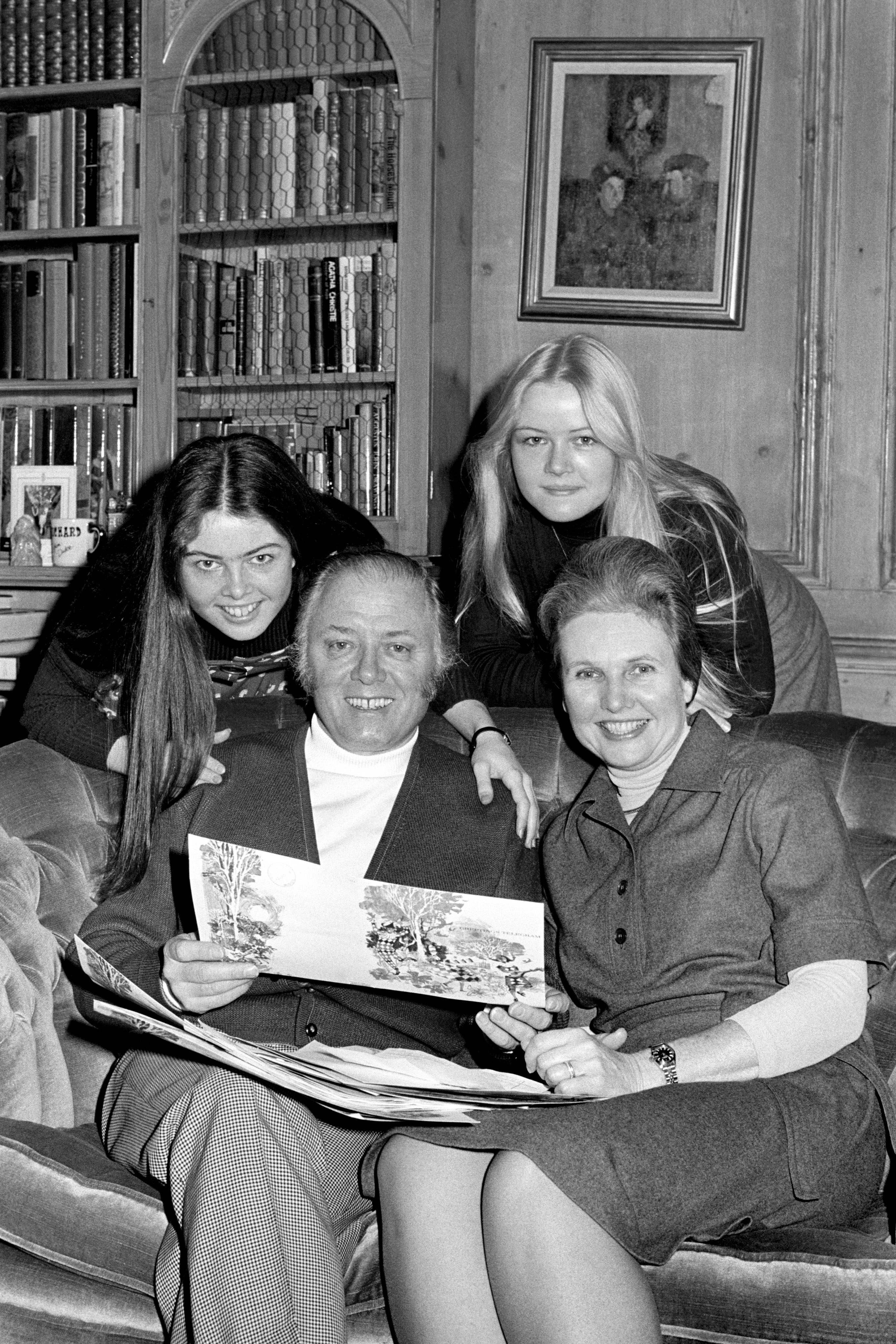 Richard Attenborough, 52, the film worlds newest knight, reads the message of congratulation today in the drawing room of his Richmond Green home. With him are his wife Sheila and daughters Charlotte, 16 (left), and Jane, 20. 1976.