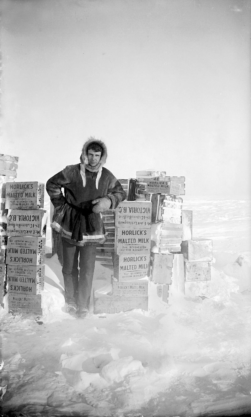Explorer Ernest de Koven Leffingwell poses with cases of Horlicks on Flaxman Island in Alaska c.1910.