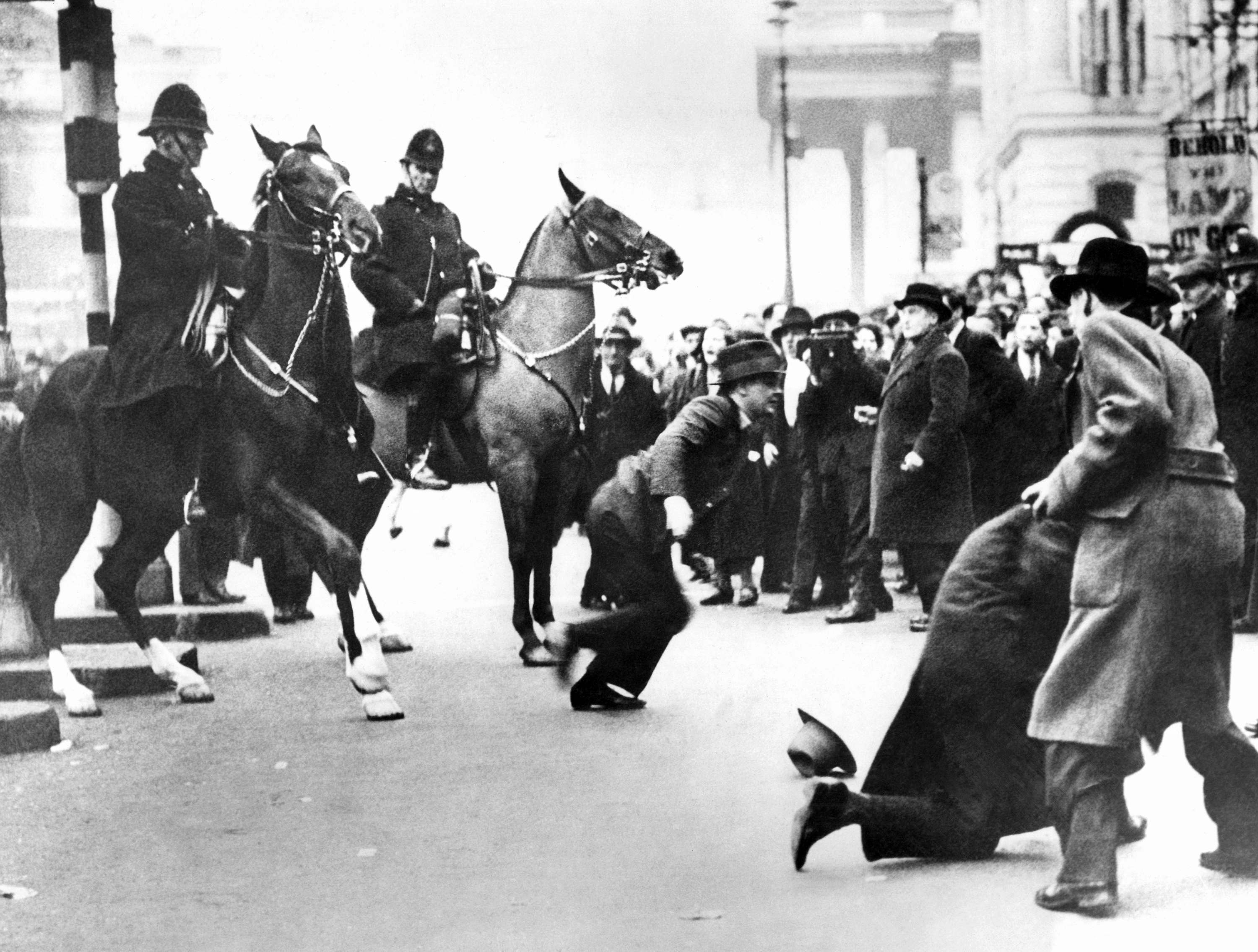 "An incident in Trafalgar Square, London on March 4, 1934, when thousands of people attended the demonstration of the so-called ""Hunger Marchers."" Mounted police are clearing the streets, and two young men here seem to have been in the way."
