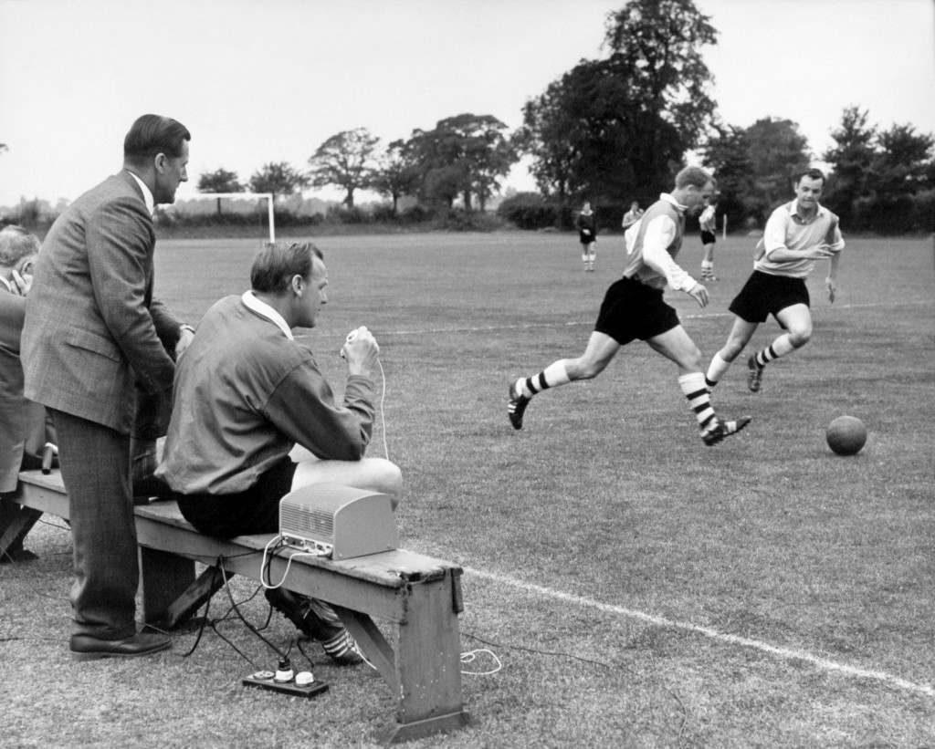 Arsenal manager George Swindin looks on as coach Ron Greenwood coaches the players by radio in the first demonstration of this system in Britain - a small earpiece is attached to a three ounce radio receiver strapped under each player's arm, allowing the coach to broadcast instructions via a transmitter on the touch line