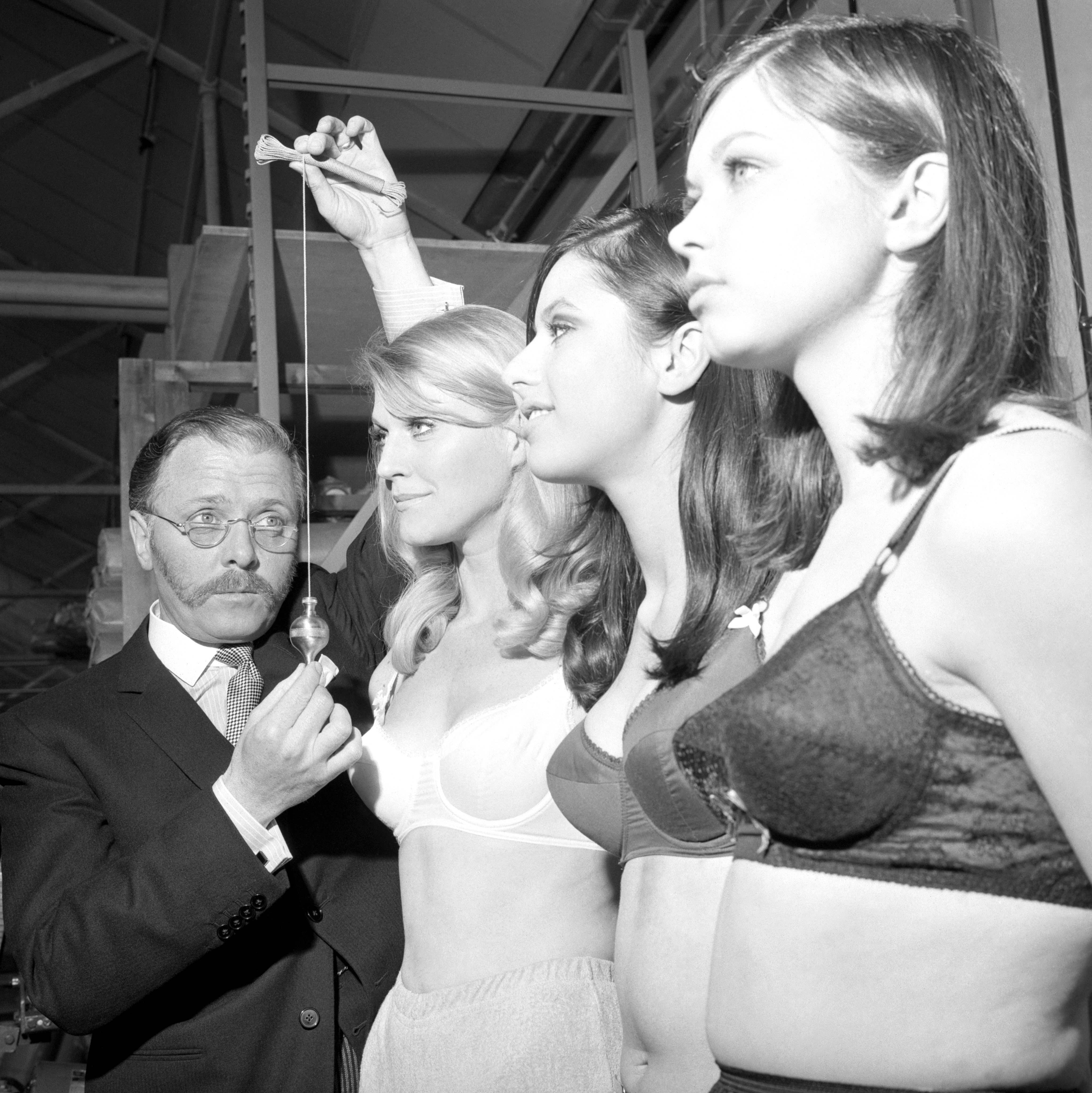 Robin Tolhurst, Sadie Cole and Margaret Bass line up at the Berlei Foundation Garment Factory in Slough to pose with Richard Attenborough, as he begins filming The Bliss of Mrs Blossom. He plays a brassiere manufacturer with an ambition to create an inflatable universal bra, 1967.