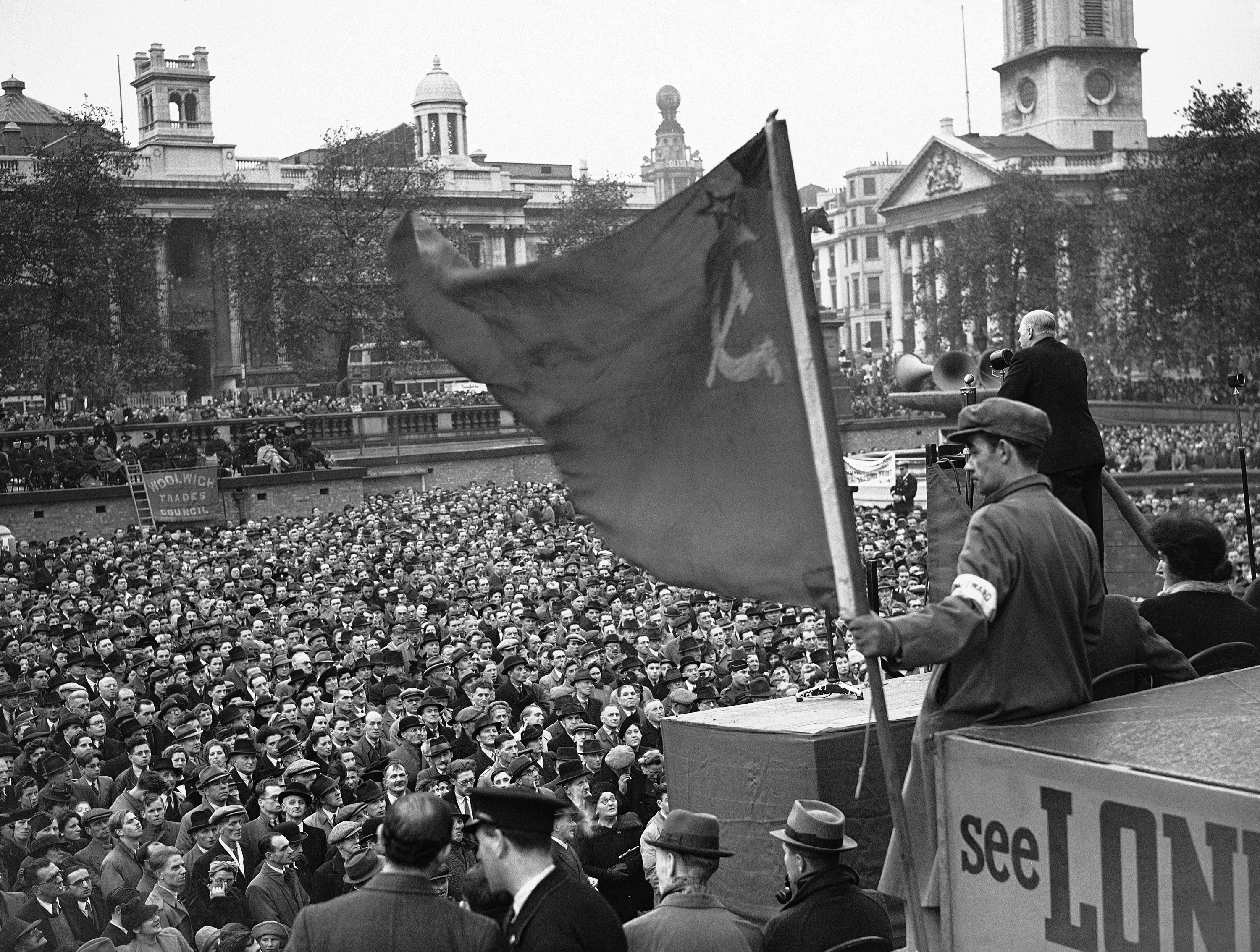 War heroes and factory workers were among those who took part in the rally in Trafalgar square, when the opening of a second front was again demanded. Thousands crowded into the square to hear the speakers who included Fred Cotton, 24 year old ex-soldier who lost both legs at Dunkirk and is now working 10 hours a day in a munition factory. A view of a section of the huge crowd with the Russian flag flying in the foreground on Oct. 25, 1942.