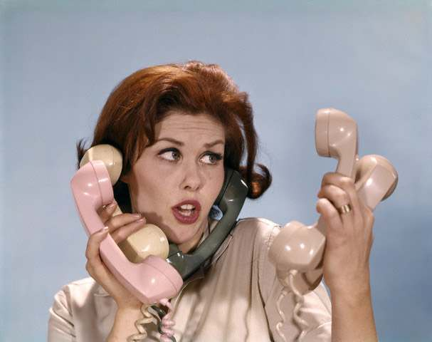 1960s Frustrated Young Redheaded Woman Trying To Answer Handle Five Telephone Receivers Studio