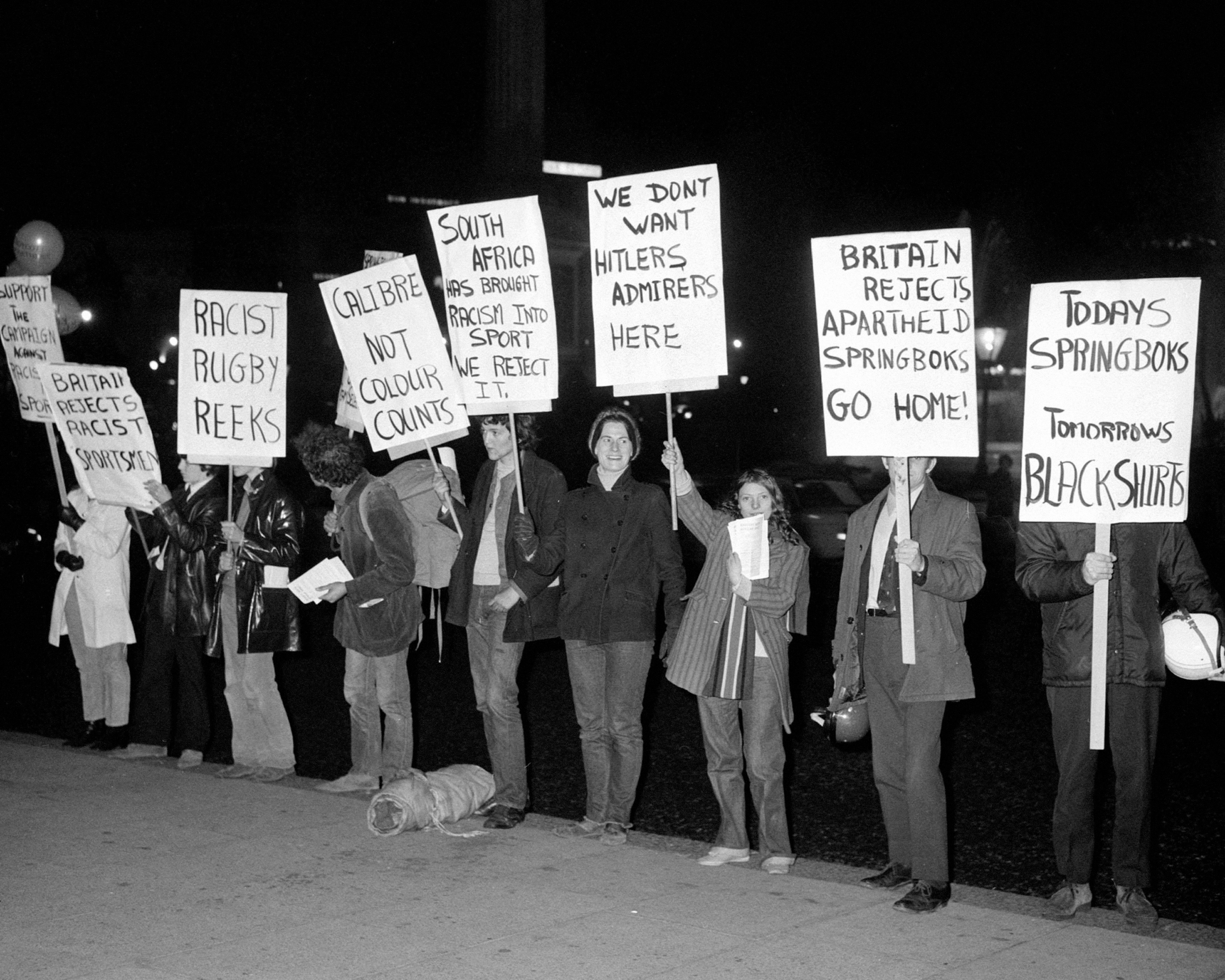 Anti-Apartheid protestors with placards outside the South African Embassy in Trafalgar Square, London, where the South African Ambassador Dr. Hendrik G. Luttig held a reception for the team.