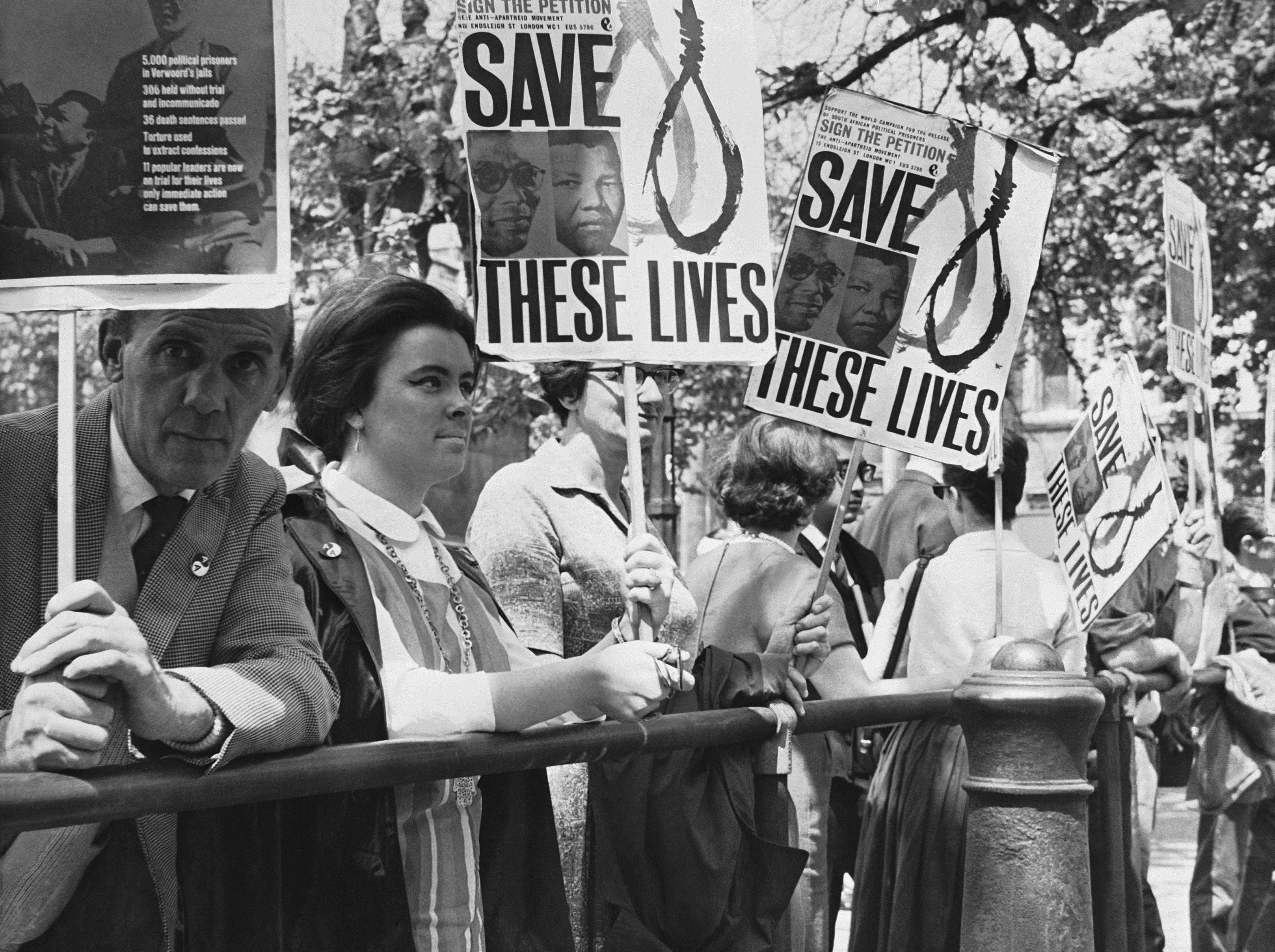 Anti-apartheid demonstrators gather outside the South African Embassy in Trafalgar Square, London, June 12, 1964, in protest against the sentence to life imprisonment of Nelson Mandela, former chief of the banned African National Congress. Mandela, 46, and seven other defendants were found guilty in the South African treason trial in Pretoria. They were sentenced today.