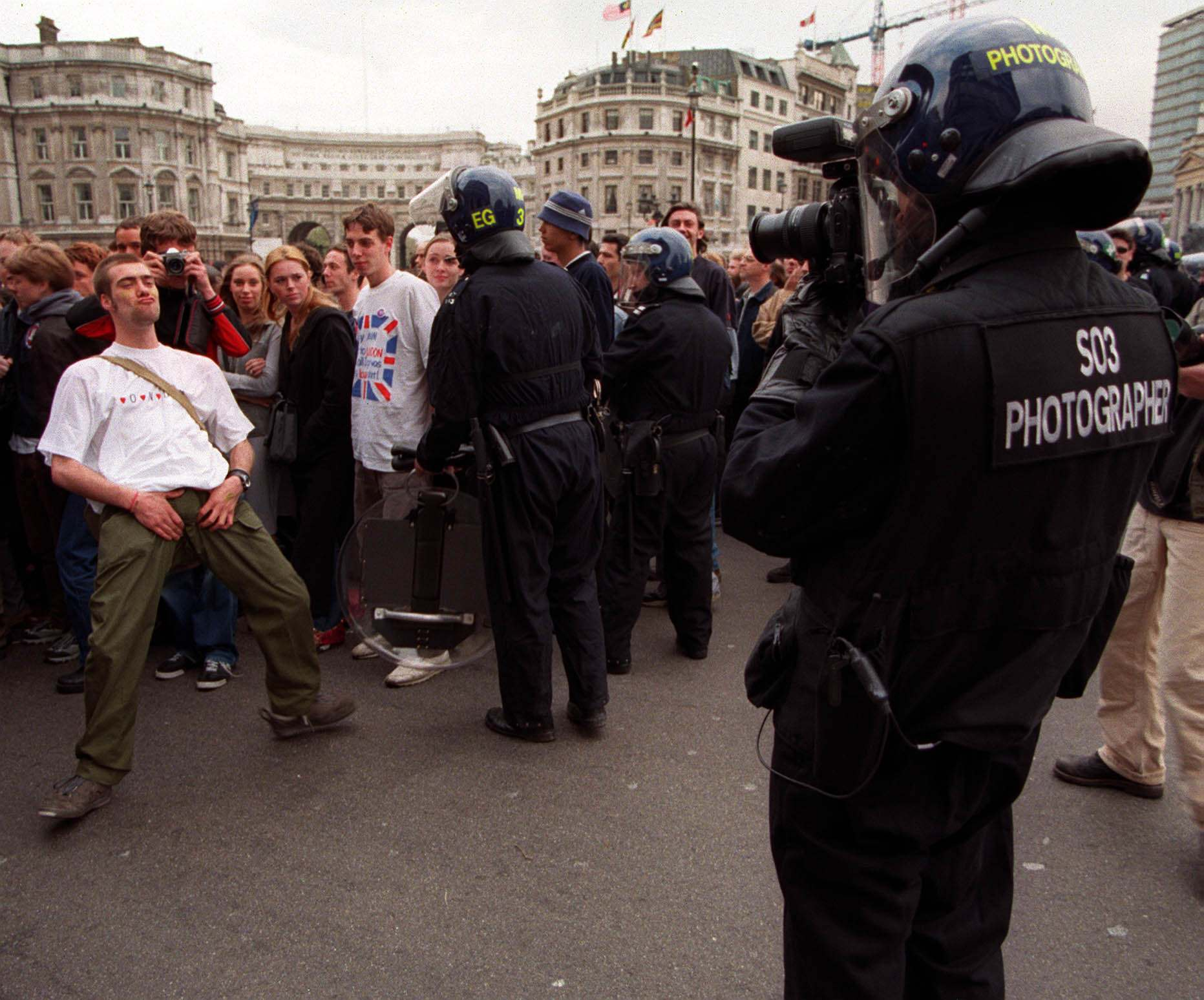 Anti-capitalist demonstrator being captured by a police surveillance photographer in Trafalgar Square, central London during their march from Parliament Square, 1/5/2000.