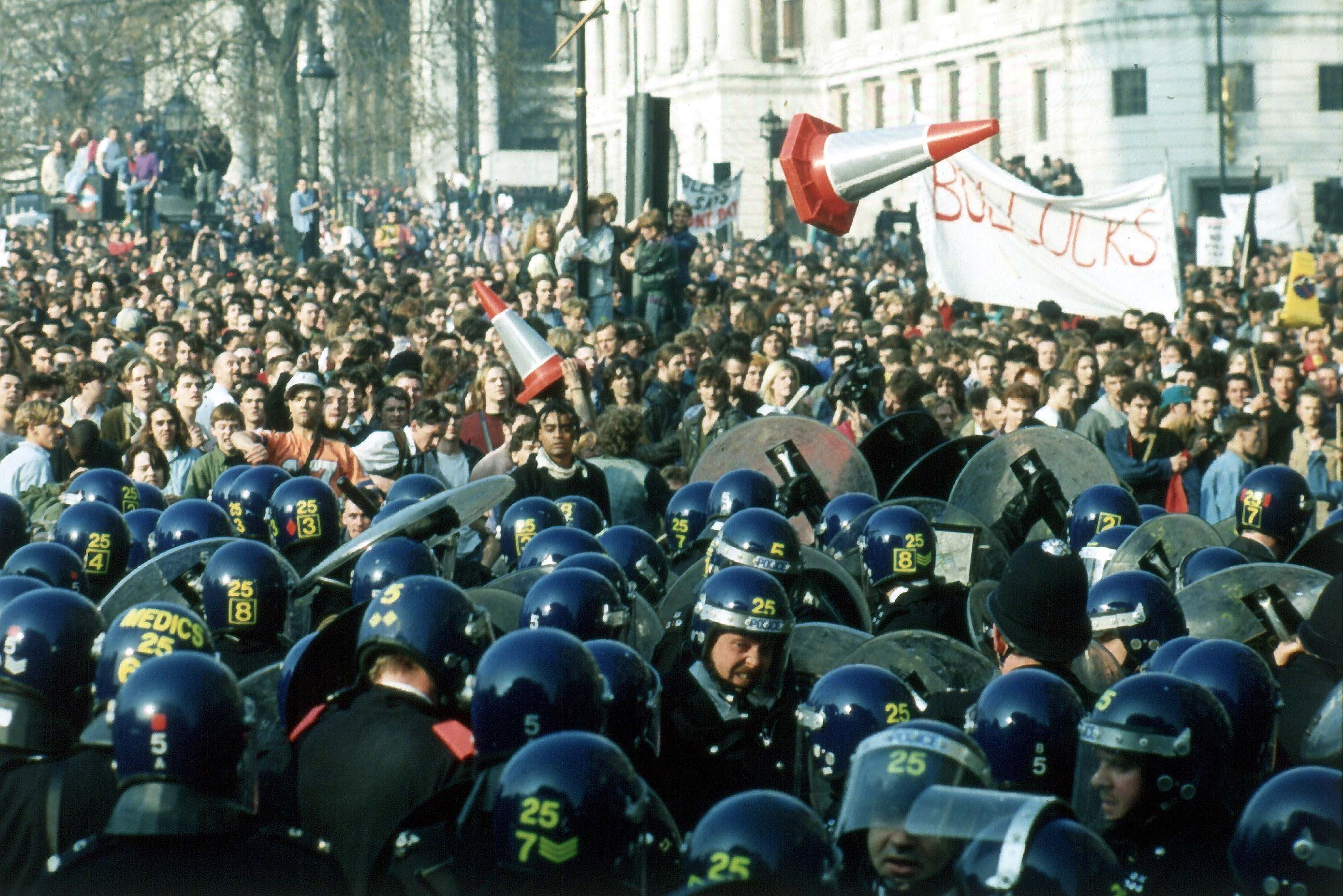British police in riot gear are pelted with road bollards and other missiles, by anti-Poll Tax demonstrators, in Trafalgar Square, London, March 31, 1990.