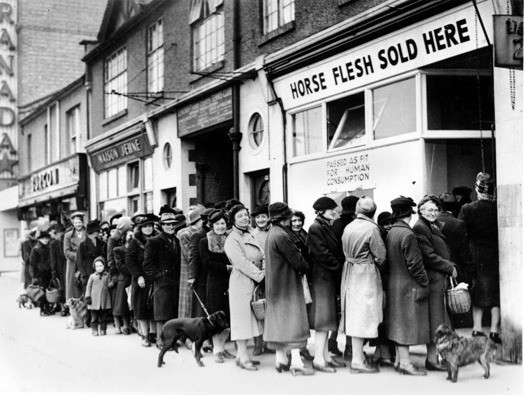 Women line up outside a butcher shop to buy meat in North Cheam, Surrey, England, on April 17, 1942 during World War II. (AP Photo)