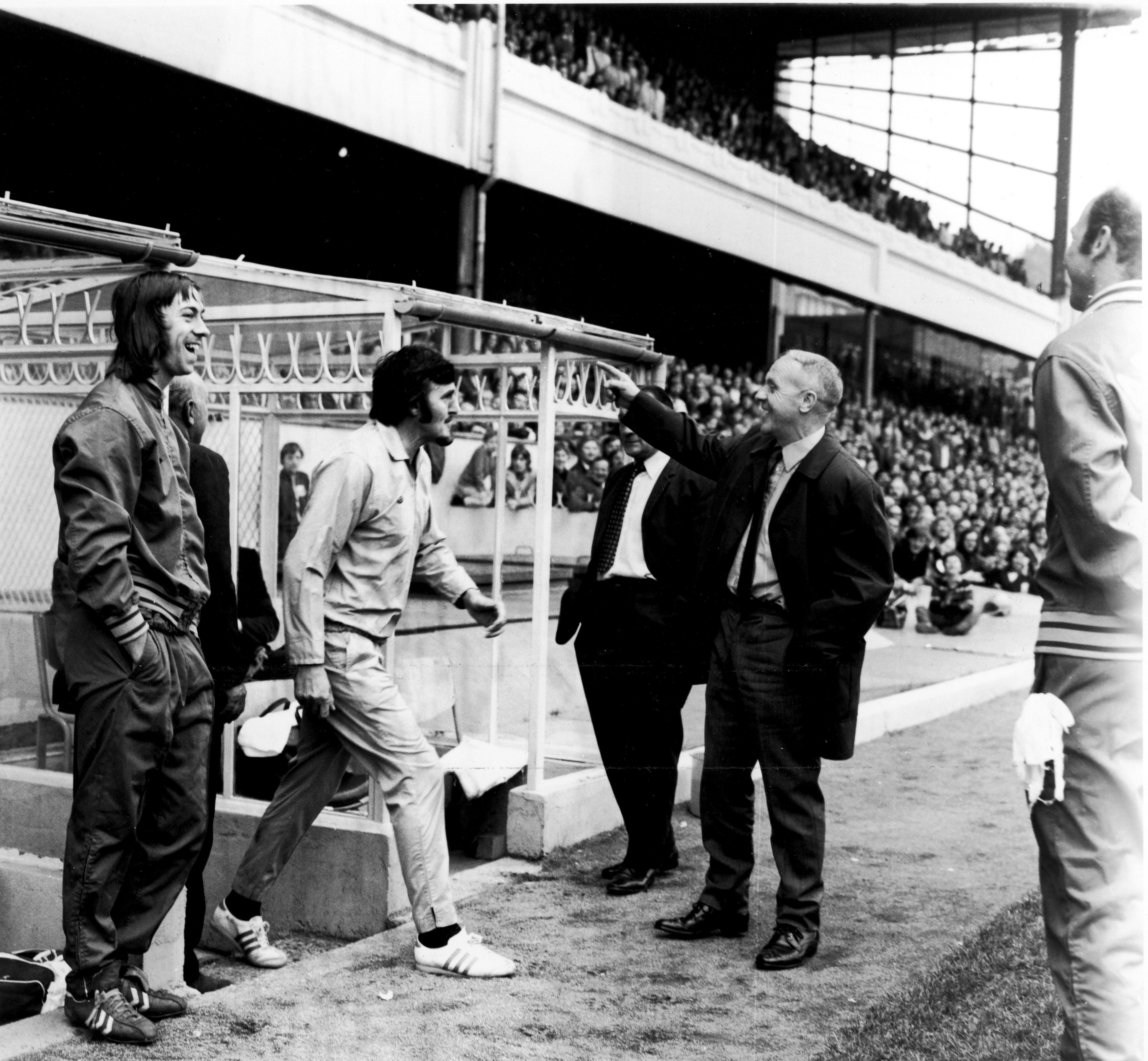 Arsenal's Charlie George (l) and Liverpool manager Bill Shankly (r) laugh their heads off as commentator Jimmy Hill (c) emerges in a sky blue tracksuit to take over from the linesman, who had limped off injured. A message was broadcast over the PA system asking for a qualified referee to take over from the linesman, and Hill was the only person to come forward. 16/9/1972