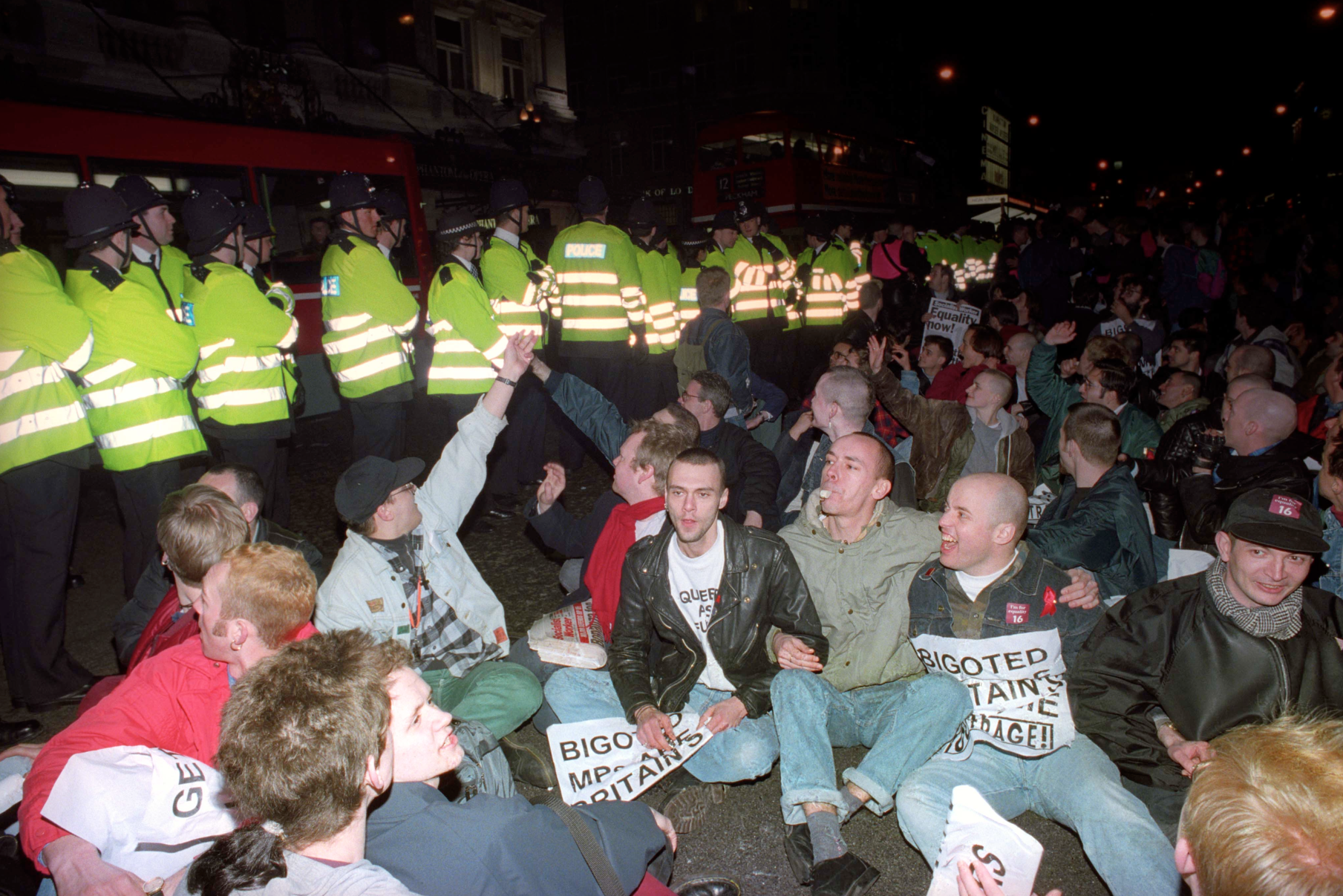 "Gay rights activists stage a sit down protest in the road  at the Haymarket, the heart of London's Theatreland, causing traffic chaos. The protest was part of an attempted march on parliament organised by ""Outrage!"". 14/3/1994"