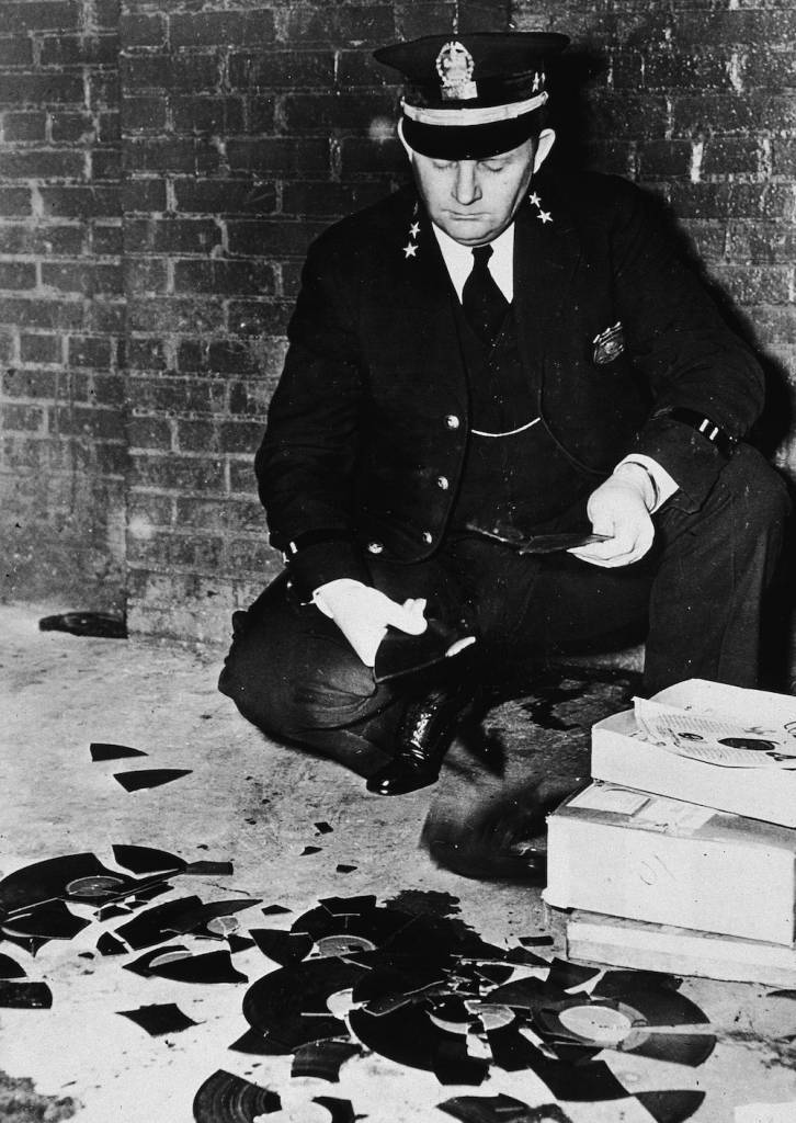 Policeman holds pieces of records that were branded obscene by the police department and smashed, Memphis, Tennessee, February 8, 1948. (Photo by Hulton Archive/Getty Images)