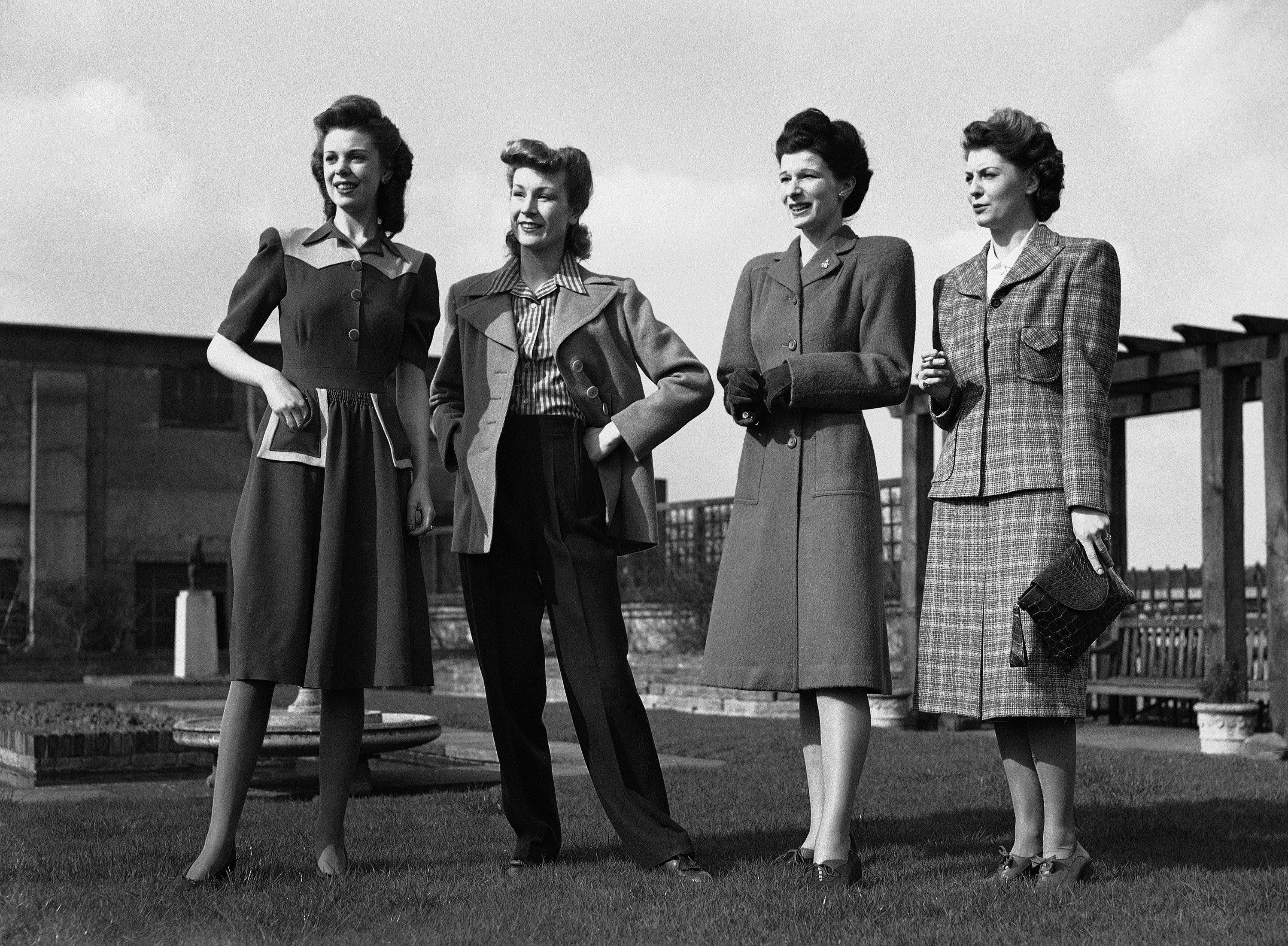 At a famous west end store, Norman Hartnell, Britain's leading dress designer, sponsored a show of the new utility fashions for the coming season on March 9, 1943. These models, said Mr. Hartnell, are designed not only for the home market but also to uphold Britain's fashion prestige abroad. From Left to right are: a 2-tone blue frock by Frances Leopold with unusual model pockets; navy blue Jaeger slacks with camel-coloured duffle coat and a wool-taffeta check blouse, a moss green coat with full yoke and inset belt with balanced pockets.