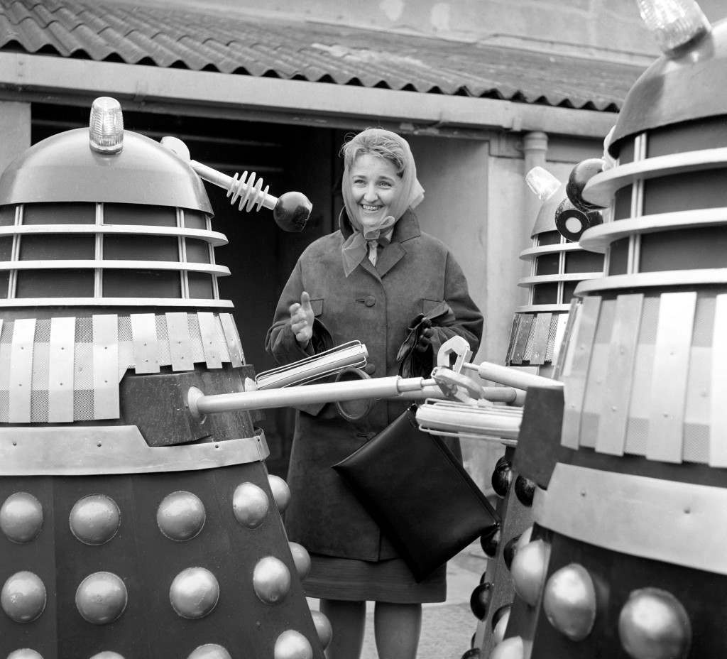 """Nadezhda Volchenko, Deputy Chief of the International Department of the Soviet Star Film Industry Committee, surrounded by Daleks on a set at Shepperton Studios, near London. The Daleks have just finished the main shooting for """"Daleks Invade Earth, 2150 AD"""". Ref #: PA.10285625 Date: 25/03/1966"""