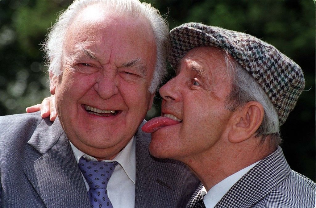 Comic legend Norman Wisdom (right) up to his old tricks as he licks newly Knighted actor,  Sir Donald Sinden, during today's (Sunday) unveiling of a plaque in Wisdom's honour in the British Comedy Society's Hall of Fame, at Pinewood studios. He is the first comedian to receive the honour to mark 50 years in showbusiness. Date: 15/06/1997