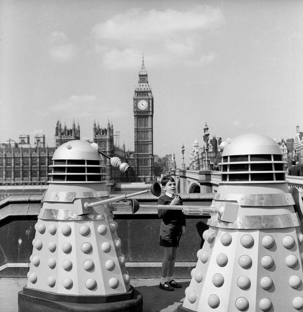 "Andrew Tuttner (8) meets two Daleks on Westminister Bridge, London. The robots were on location for the new BBC series of ""Dr Who"". 5/2/99: The Daleks will appear on Millennium stamps due to be issued Summer 1999 by the Royal Mail. * The other three stamps in the entertainers series are expected to feature Bobby Moore holding the World Cup aloft, Charlie Chaplin and former rock legend Freddie Mercury. Ref #: PA.1162284 Date: 20/08/1964"