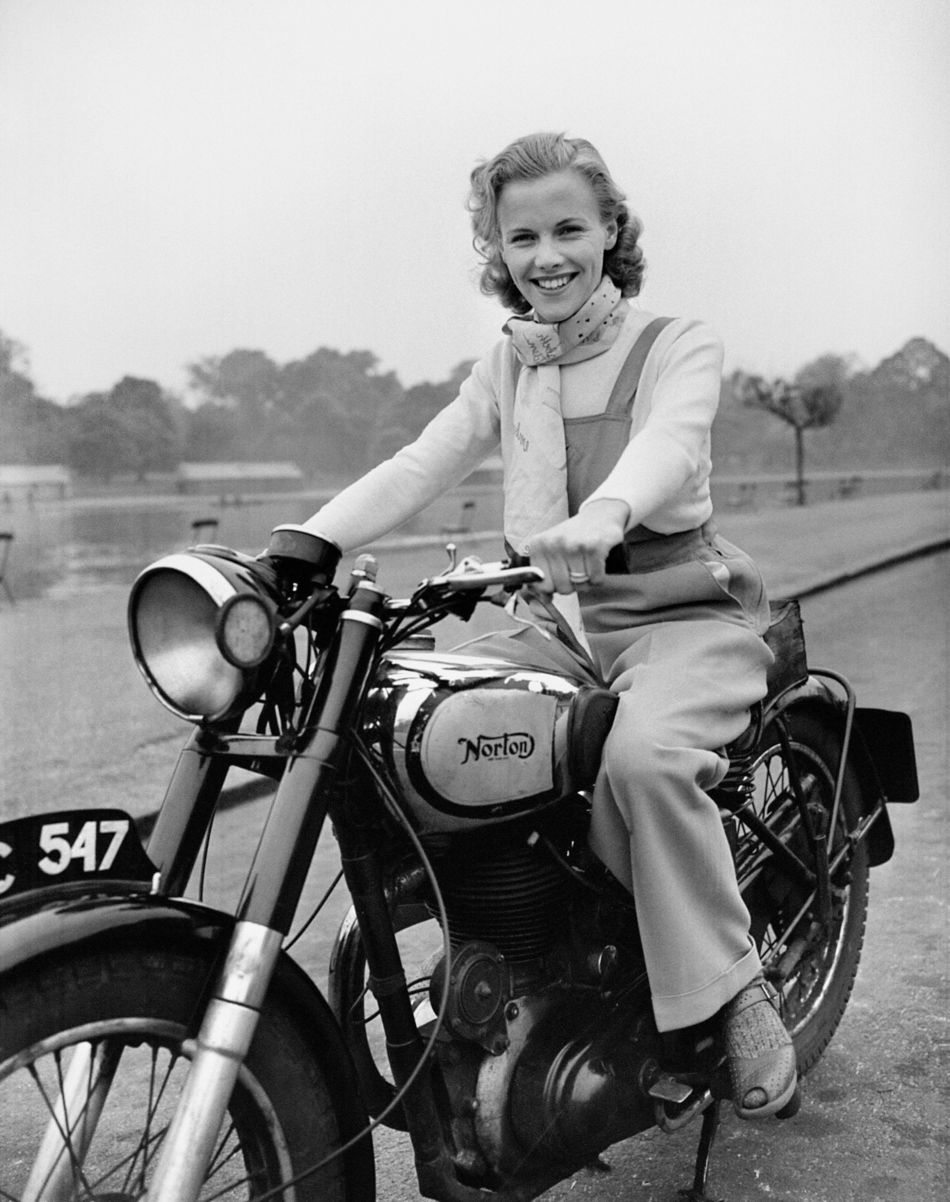 London-born film actress Honor Blackman, age 23, riding her Norton Big Four motorcycle through Hyde Park in London. 9/5/1949