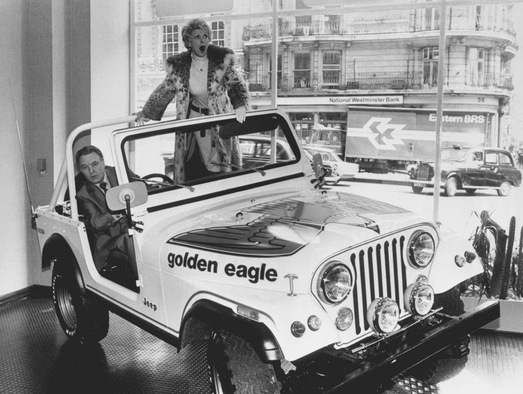 "Actress Elaine Stritch and actor Donald Sinden, stars of the television series ""Two's Company"", in a Jeep while they launch the opening of a new London showroom by the American-based firm. They are trying out one of the latest models, which is a far cry from the camouflaged jobs which stormed the beaches and battlefields of World War Two. Date: 17/05/1978"