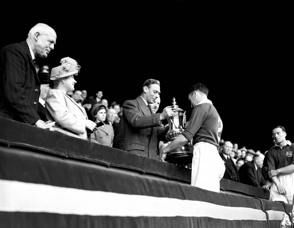 ohnny Carey, Manchester United Captain receives the FA Cup from HM King George VI as the Queen looks on. Manchester United won 4-2 at Wembley.