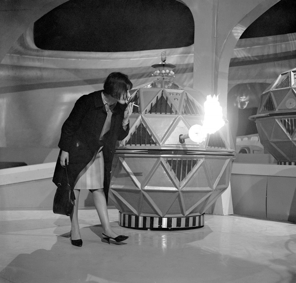 Verity Lambert lighting a cigarette from one of the mechanoid flame guns from the new Dalek series. archive-439301 Date: 15/04/1965