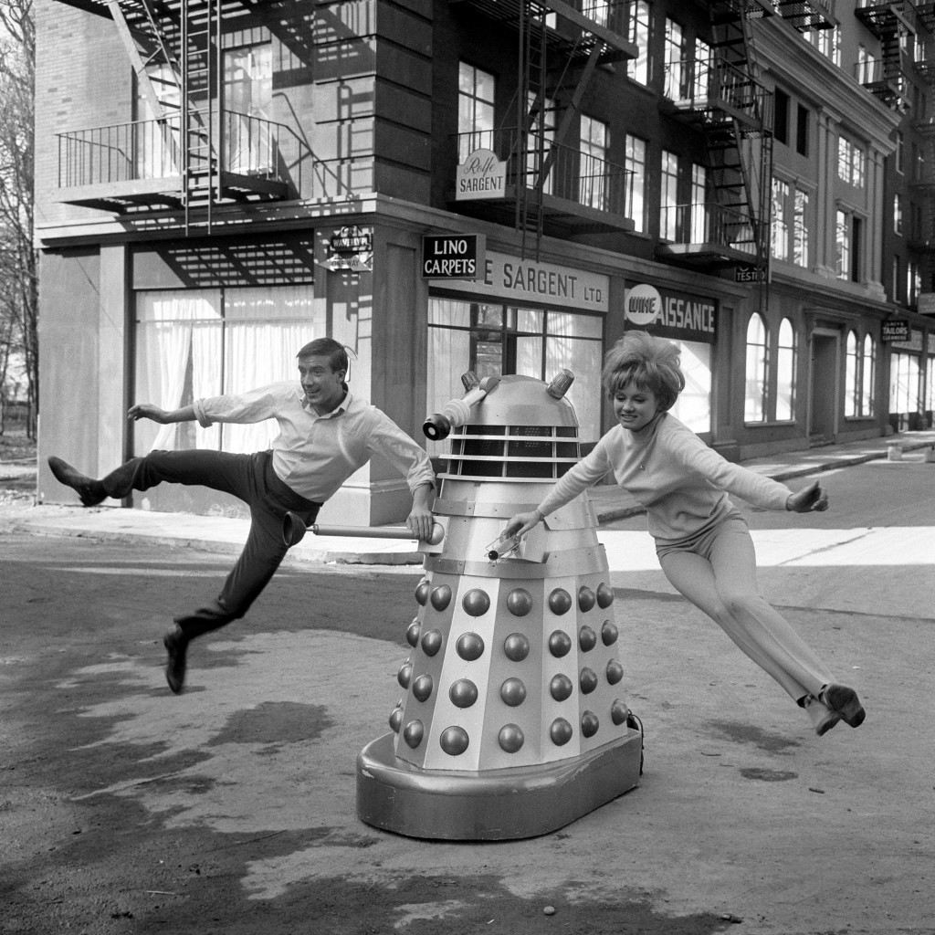 """Swinging on a Dalek at Shepperton Studios are Roy Castle and Jennie Linden, seen practising a dance routine for """"Dr Who and the Daleks"""", a film based on the BBC television science fiction serial and now being made at Shepperton. Roy Castle plays Ian and 22 year old Jennie plays his girlfriend Barbara, Dr Who's granddaughter. Dr Who is played by Peter Cushing. Ref #: PA.8644834 Date: 10/03/1965"""