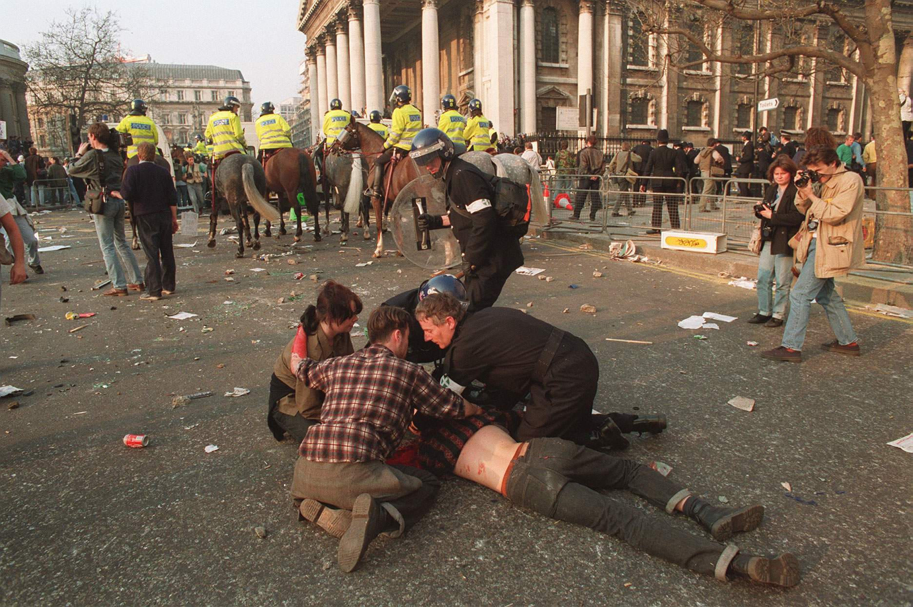 Police in riot gear treat an injured protester in Trafalgar Square, London, when rioting broke out after an anti-poll tax demonstration. 31/3/1990