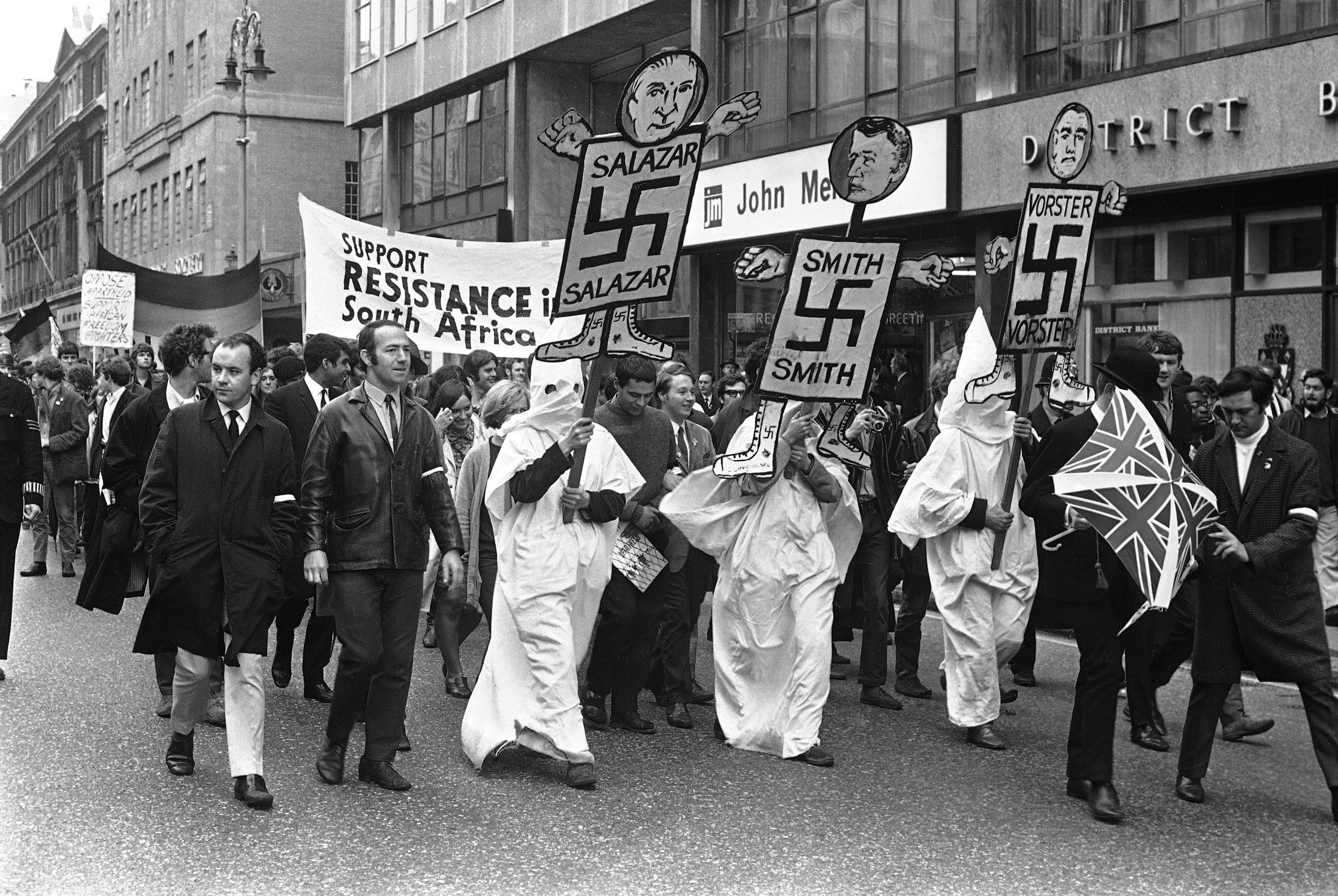 Members wearing white hoods and gowns attending the anti-apartheid movement's South African Freedom Day Rally, hold aloft their banners with Nazi symbols and pictures of Salazar, Smith and Vorster, as they enter Trafalgar Square, London, on June 23, 1968. (AP Photo/Kemp)